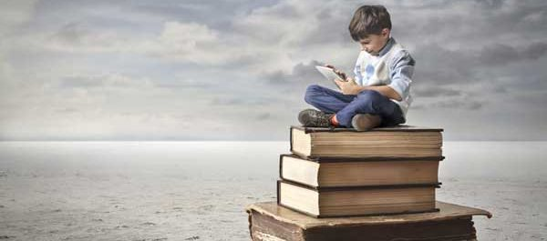 Child sitting on stack on books reading