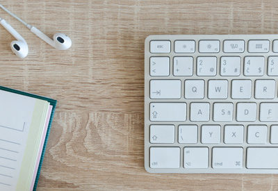 Keyboard, notepad, apple earphones.